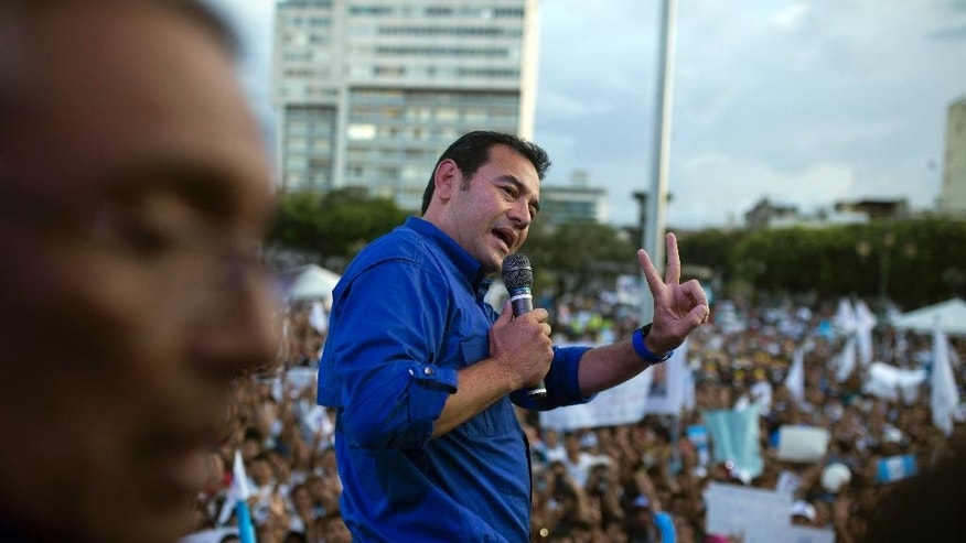 Jimmy Morales, the National Front of Convergence party presidential candidate, gives a victory sign as he speaks to supporters during a campaign rally in Guatemala City, Thursday, Oct. 22, 2015. In Sunday's presidential runoff, Morales, who boasted of his outsider status on the campaign trail, faces Sandra Torres, a businesswoman and longtime political party operative who in a previous campaign divorced former President Alvaro Colom to try to get around a rule barring presidential relatives from seeking the office. (AP Photo/Luis Soto)