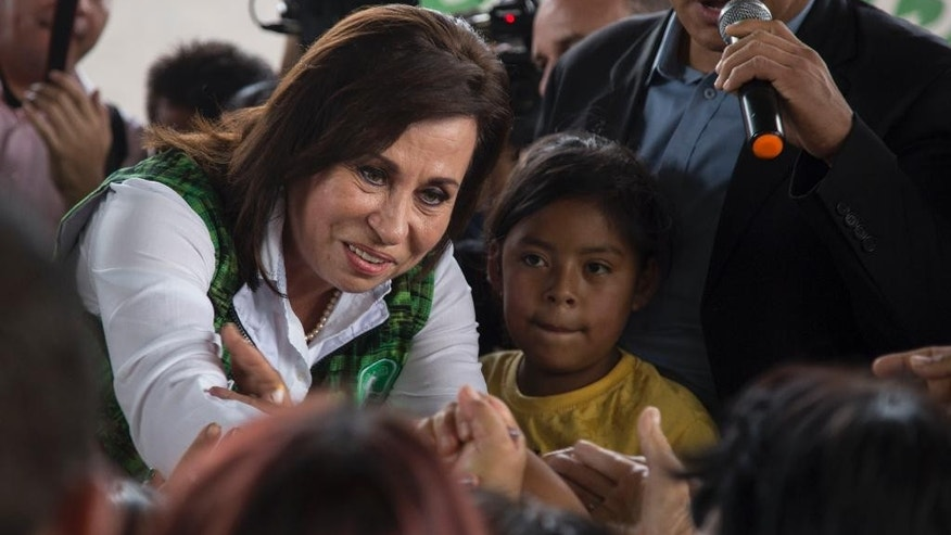 Former first lady Sandra Torres, who's running for president with the National Unity of Hope party, shakes hands with supporters during her last campaign rally at the El Amparo neighborhood in Guatemala City, Friday, Oct. 23, 2015. The former first lady and a TV comic will vie for Guatemala's presidency Sunday, and the winner will face a tide of public anger at politicians that already drove the last elected president and vice president from office in disgrace. (AP Photo/Luis Soto)