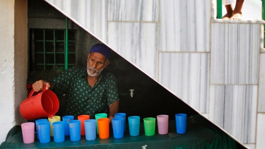 A Bangladeshi man pours water in glasses for Shiite Muslims at the site of an explosion in Dhaka, Bangladesh, Saturday, Oct. 24, 2015. As thousands of Shiite Muslims gathered for a religious procession before dawn Saturday, unidentified attackers hurled home-made bombs that exploded in the crowd in Bangladesh's capital. (AP Photo/A.M. Ahad)