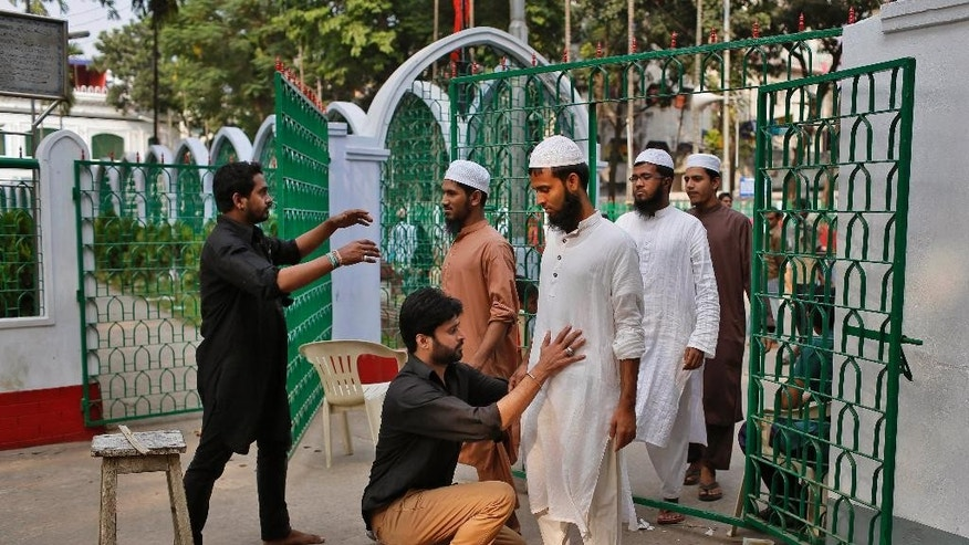 Volunteers check visitors at the entrance of a shrine, the site of an explosion, in Dhaka, Bangladesh, Saturday, Oct. 24, 2015. As thousands of Shiite Muslims gathered for a religious procession before dawn Saturday, unidentified attackers hurled home-made bombs that exploded in the crowd in Bangladesh's capital. (AP Photo/A.M. Ahad)