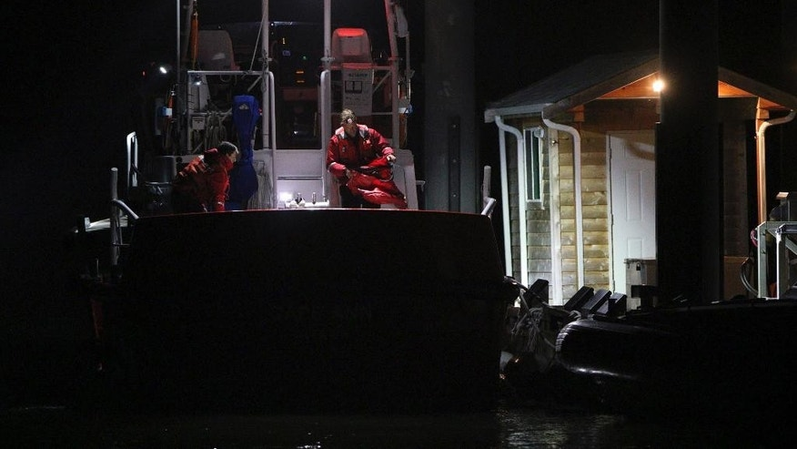 Canadian Coast Guard crew arrive at a dock in Tofino, west coast of Vancouver, Canada, early Monday, Oct. 26, 2015, following a search and rescue operation. A whale watching boat with 27 people on board sank off Vancouver Island on Sunday, Canadian authorities said. (Chad Hipolit/The Canadian Press via AP)