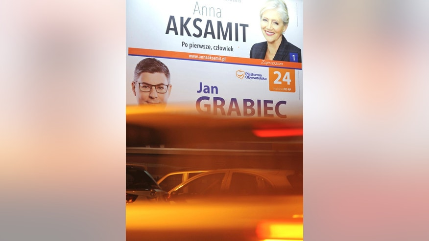 Cars drive past election posters in Warsaw evening, Poland, Saturday, Oct. 24, 2015, one day ahead of the parliamentary elections in which Poles will choose 460 lawmakers to the lower chamber and 100 senators. (AP Photo/Alik Keplicz)