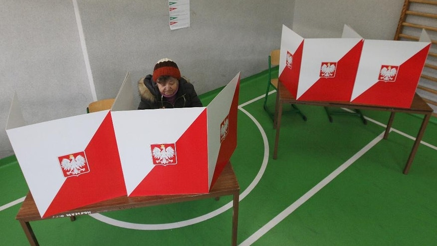 A woman reads her ballot before casting during general elections in Warsaw, Poland, Sunday, Oct. 25, 2015.  Poles voted Sunday in a parliamentary election that is expected to shift power from a centrist and pro-market party to a socially conservative and somewhat Euro skeptic party that favors more welfare spending to help the poor.(AP Photo/Czarek Sokolowski)