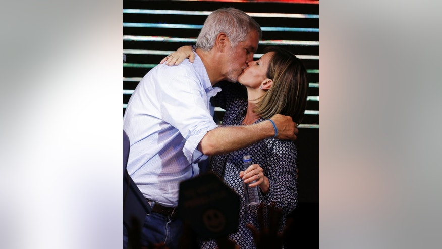 Enrique Penalosa kisses his wife Liliana Sanchez as he celebrates being proclaimed the new mayor of Bogota, Colombia, Sunday, Oct. 25, 2015. Penalosa was declared the winner by the electoral authorities with 99% of the vote counted. He took the lead ahead of his closest contender the former defense minister Rafael Pardo. (AP Photo/Fernando Vergara)