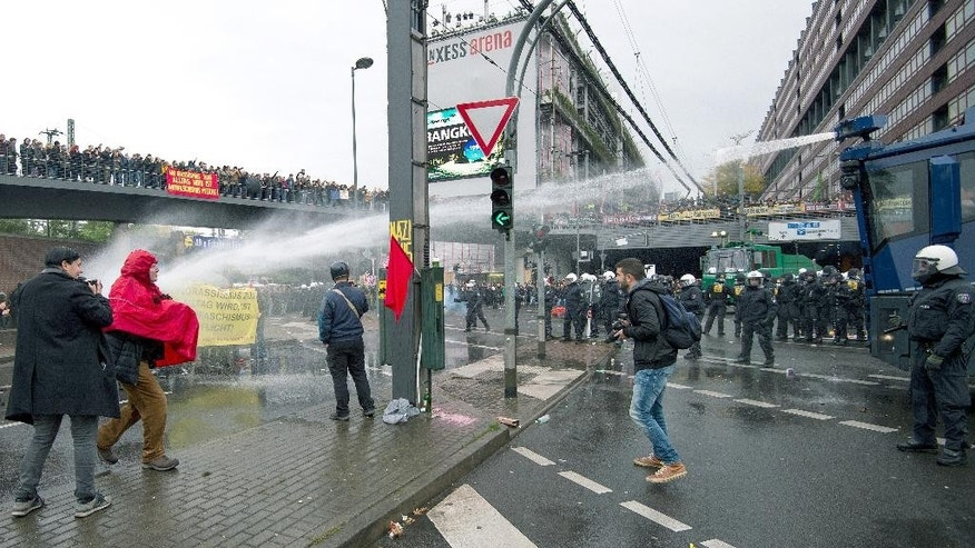 Police use a water cannon against counter demonstrators protesting against a right-wing demonstration  in Cologne, Germany, Sunday Oct. 25,  2015. A demonstration, organized by far-right groups and members of Germany's football hooligan scene, named HOGESA,  is observed by about  3,500 policemen to secure the demonstration and counter protests in the city.   (Marius Becker/dpa via AP)