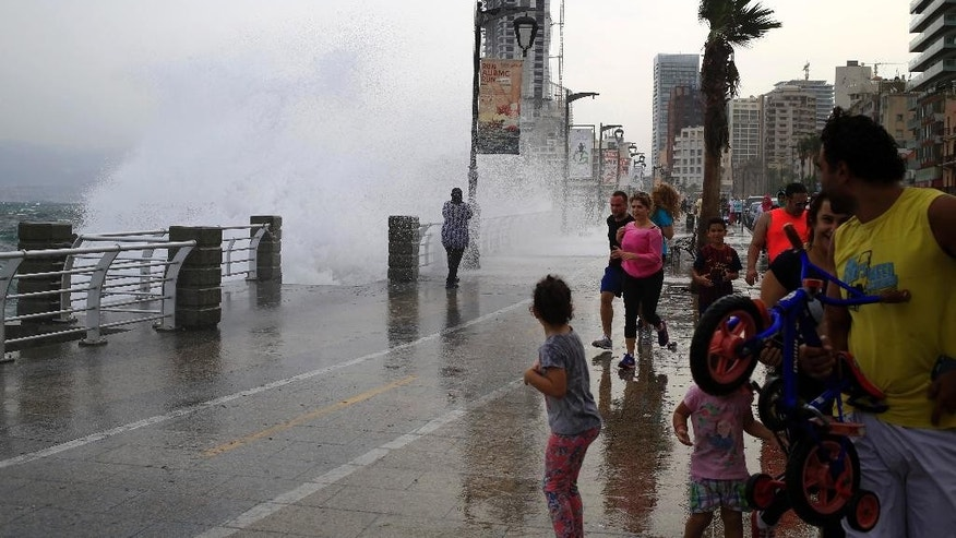 Lebanese people try to avoid getting soaked by high waves crashing on the seafront at the Corniche, or waterfront promenade, in Beirut, Lebanon, Sunday, Oct. 25, 2015. (AP Photo/Hassan Ammar)