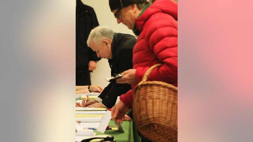 Jaroslaw Kaczynski, the leader of the conservative opposition Law and Justice party prepares to cast his ballot at a polling station in Warsaw, Poland on Sunday, Oct. 25, 2015. Poles voted Sunday in a parliamentary election that is expected to shift power from a centrist and pro-market party to a socially conservative and somewhat Euroskeptic party that favors more welfare spending to help the poor.  (AP Photo/Czarek Sokolowski)