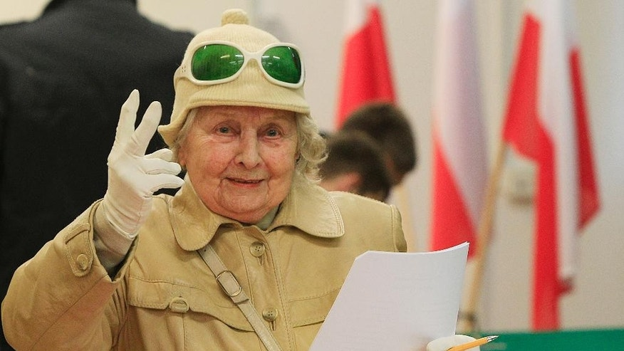 A woman rprepares to cast her ballot at a polling station in Warsaw, Poland on Sunday, Oct. 25, 2015. Opinion polls showed Law and Justice ahead of the ruling Civic Platform party, In Sunday's elections.  (AP Photo/Czarek Sokolowski)