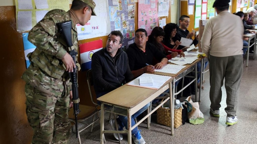 A soldier talks to a polling station official as they prepare to open in Tigre, outskirts of Buenos Aires, Argentina, Sunday Oct. 25, 2015. Argentines are weighing continuity versus a financial overhaul in Sunday's elections as they pick the successor to President Cristina Fernandez, a polarizing leader who dominated national politics for 12 years.(AP Photo/Enric Marti)