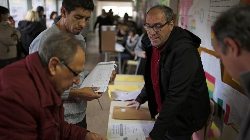 Officials at a polling station prepare ballots for voting in Tigre, outskirts of Buenos Aires, Argentina, Sunday Oct. 25, 2015. Argentines are weighing continuity versus a financial overhaul in Sunday's elections as they pick the successor to President Cristina Fernandez, a polarizing leader who dominated national politics for 12 years.(AP Photo/Enric Marti)