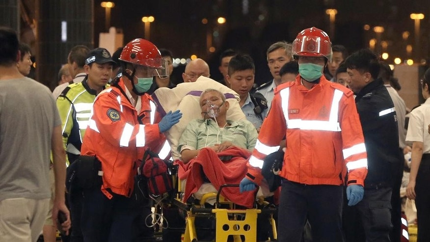 An injured passenger of a high-speed ferry is escorted by rescuers to a hospital after getting on shore in Hong Kong Monday, Oct. 26, 2015. More than 120 people were injured when the ferry traveling from the Asian gambling hub of Macau to Hong Kong slammed into an object floating in the water, authorities said Monday. (Apple Daily via AP) HONG KONG OUT, TAIWAN OUT