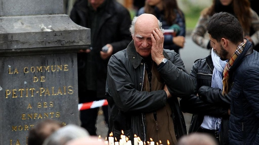 The families and relatives of the victims gather around candles place at a monument in Petit Palais, southwestern France, Sunday, Oct. 25, 2015, to pay tribute to the  victims of the bus crash last Friday in Puisseguin. A truck and a bus transporting retirees on a day trip collided and caught fire Friday on a country road in wine country in southwest France, killing over 40 people and gravely injuring at least four others, authorities said. (AP Photo/Bob Edme)