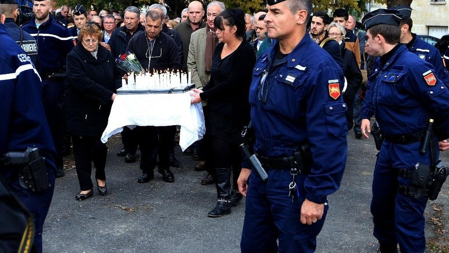 The families and relatives of the victims carry candles in procession in Petit Palais, southwestern France, Sunday, Oct. 25, 2015, to pay tribute to the  victims of the bus crash last Friday in Puisseguin. A truck and a bus transporting retirees on a day trip collided and caught fire Friday on a country road in wine country in southwest France, killing over 40 people and gravely injuring at least four others, authorities said. (AP Photo/Bob Edme)