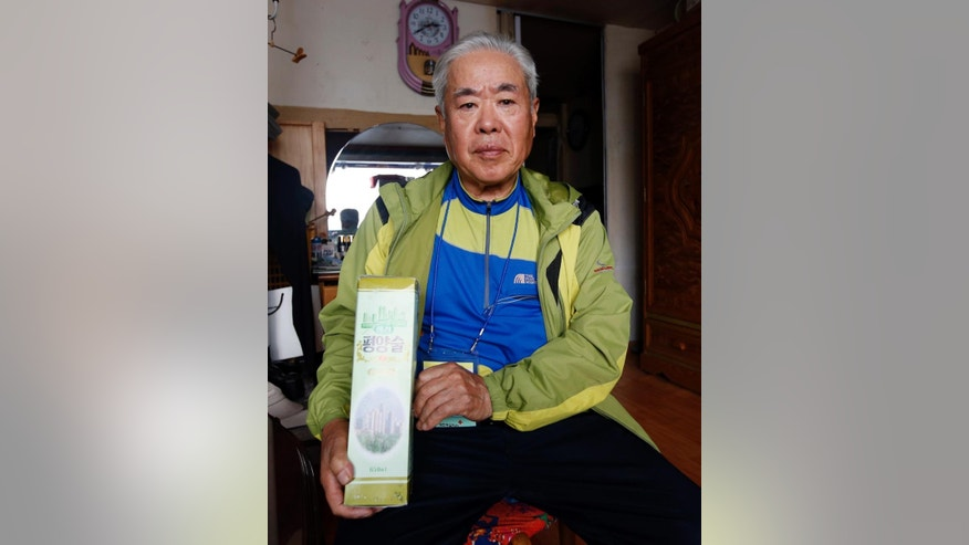 In this Friday, Oct. 23, 2015 photo, South Korean Lee Cheon-wu, a 78-year-old retired farmer, who recently returned from North Korea after met with his North Korean sister Ri Mun Wu, 84, during the Separated Family Reunion Meeting, poses with a bottle of liquor from his sister, for a photograph at his home in Seoul, South Korea. This weekend, scores of Koreans on both sides of the border are holding reunions with family members divided by the Korean War some six decades ago. Most have not seen each other since then, and may never again. (AP Photo/Lee Jin-man)