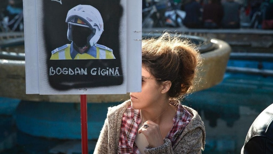 A woman holds a banner that bearing the name of a police motorcyclist during a protest demanding the resignation of Interior Minister Gabriel Oprea in Bucharest, Romania, Sunday, Oct. 25, 2015. Romania's president has called on the prime minister and interior minister to address public anger over the death of a police motorcyclist who died during a traffic mission after hitting a large hole in the road while escorting Interior Minister Oprea.(AP Photo/Vadim Ghirda)