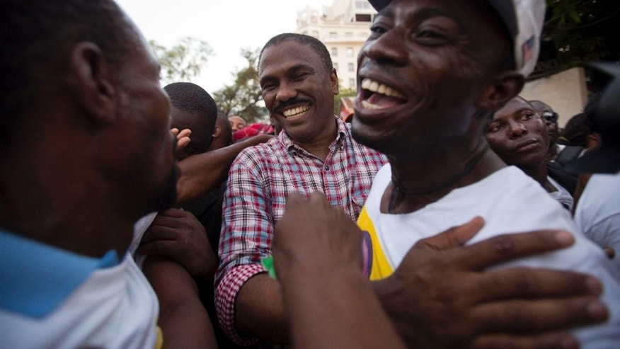 Presidential candidate Jude Celestin from the LAPEH political party, in checkered shirt, greets supporters during a rally in the Port-au-Prince neighborhood of Petion-Ville, Haiti, Thursday, Oct. 22, 2015. Former head of the state construction company, Celestin was the government-backed candidate in the 2010 presidential contest. Disputed preliminary results had Celestin edging out eventual winner Michel Martelly for a runoff spot, but international pressure led Haitian authorities to review the count and eliminate Celestin. (AP Photo/Dieu Nalio Chery)