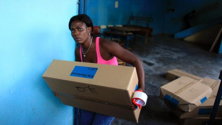 A woman carries a box of electoral material in a polling station in Port-au-Prince, Haiti, Saturday, Oct. 24, 2015. Haitians are going to the polls Sunday to pick Haiti's next president, two-thirds of the Senate, the entire Chamber of Deputies and local offices. The Oct. 25 vote is expected to clear the sprawling presidential field for a runoff Dec. 27 between the top two finishers. (AP Photo/Ricardo Arduengo)