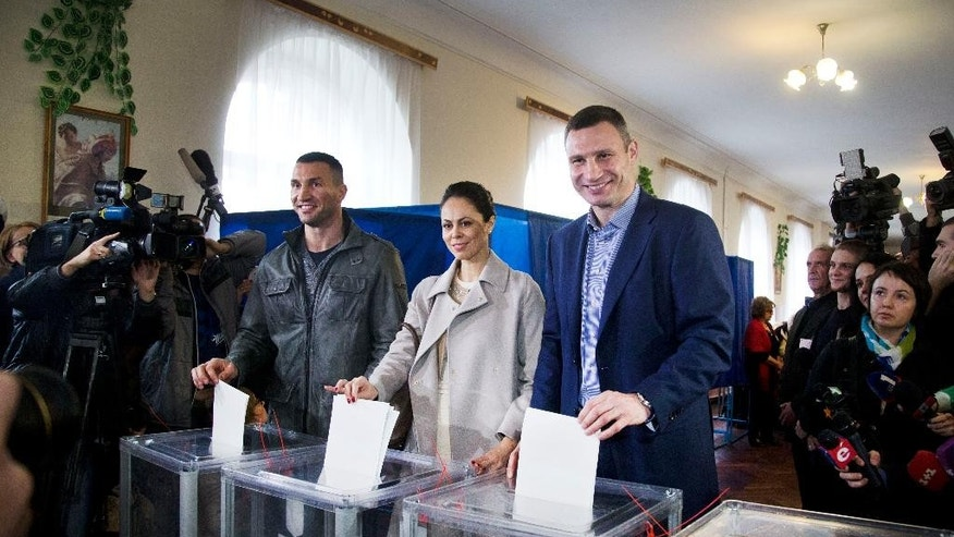 Kiev's current mayor and former heavyweight boxing champion Vitali Klitschko, right, his wife Natalia Klitschko, center, and his brother boxing heavyweight world champion Wladimir Klitschko vote at a polling station in an regional and local elections  in Kiev, Ukraine, Sunday, Oct. 25, 2015. Polling stations opened in Ukraine on Sunday for regional and local elections across the country, except for the separatist-held regions in the east. According to local media, Kiev's current mayor and former heavyweight boxing champion Vitali Klitschko is expected to win in the capital. (AP Photo/Efrem Lukatsky)