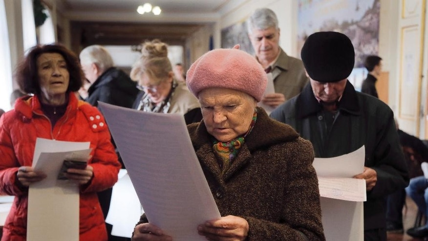 Voters read their ballots at a polling station in Kiev, Ukraine, Sunday, Oct. 25, 2015. Polling stations opened in Ukraine on Sunday for regional and local elections across the country, except for the separatist-held regions in the east. (AP Photo/Efrem Lukatsky)