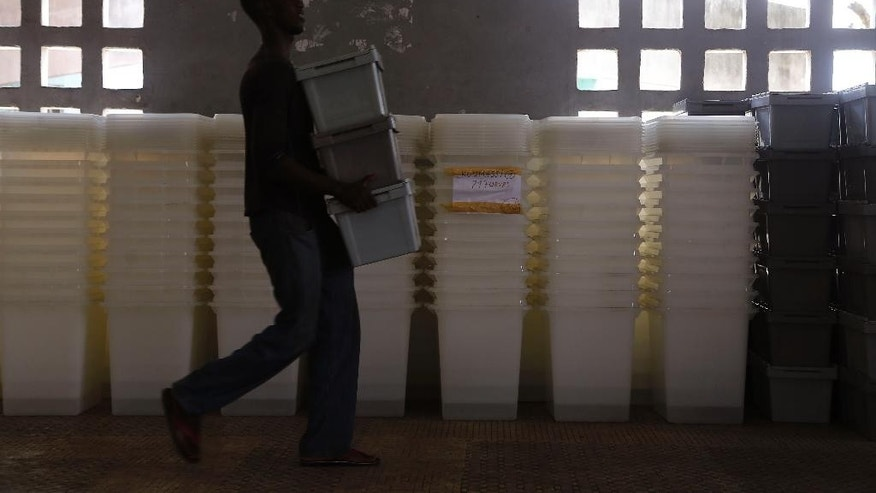 Election workers carry election material for distribution to a holding area at a community center in Abidjan, Ivory Coast, Saturday, Oct. 24, 2015.  Ivory Coast's president Alassane Ouattara is widely expected to win a second term as the West African nation votes Sunday, five years after a disputed poll that spilled over into the worst violence the country has experienced since independence. (AP Photo/Schalk van Zuydam)