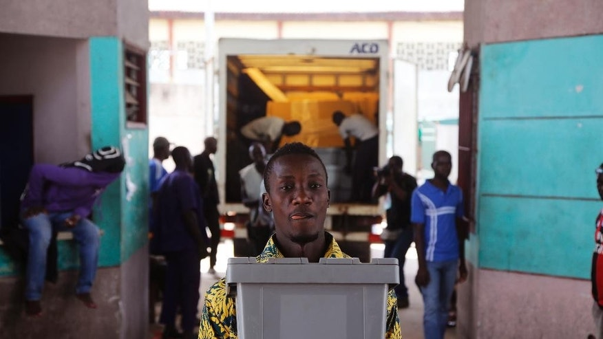An election worker carries election material at a community center in Abidjan, Ivory Coast, Saturday, Oct. 24, 2015.  Ivory Coast's president Alassane Ouattara is widely expected to win a second term as the West African nation votes Sunday, five years after a disputed poll that spilled over into the worst violence the country has experienced since independence. (AP Photo/Schalk van Zuydam)