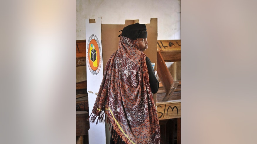 A Tanzanian woman prepares to cast her vote in the presidential election, at a polling station in Dar es Salaam, Tanzania Sunday, Oct. 25, 2015. Voting has started in Tanzania's general elections in which the ruling party faces a strong challenge from a united opposition. (AP Photo/Khalfan Said)