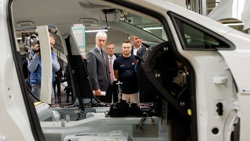 Volkswagen CEO Matthias Mueller,  center, looks at the assembly  line during a tour of the VW plant  in Wolfsburg, Germany Wednesday Oct. 21, 2015.  ( Julian Stratenschulte/Pool Photo via AP)