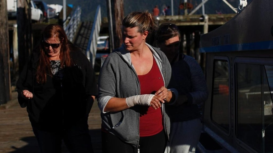 Jenn Newman, one of the survivors rescued after the Leviathan II sank, visits First St. dock and the G.I. Charles boat that rescued her, before leaving Tofino, British Columbia, Monday, Oct. 26, 2015. The whale watching boat with over two dozen people on board sank Sunday off Vancouver Island, the British Foreign Minister said Monday, killing multiple people. (Chad Hipolito/The Canadian Press via AP) MANDATORY CREDIT