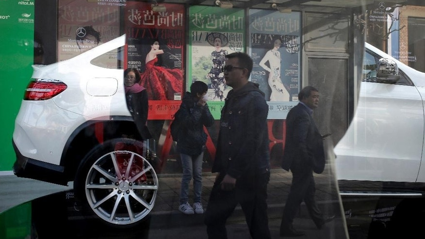 People are reflected on a window as they walk past fashion magazine posters near a Mercedes-Benz SUV model on display at a showroom for the China Fashion Week at the 798 Art Gallery in Beijing, Monday, Oct. 26, 2015. Facing pressure to shore up sagging economic growth, Chinese leaders are gathered this week to draw up a new blueprint to guide development through the end of this decade. (AP Photo/Andy Wong)
