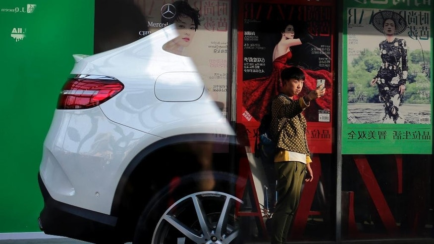 "A man is reflected on a Mercedes-Benz showroom's window glass as he takes a ""selfie"" near fashion magazine posters on display at the 798 Art Gallery in Beijing, Monday, Oct. 26, 2015. Facing pressure to shore up sagging economic growth, Chinese leaders are gathered this week to draw up a new blueprint to guide development through the end of this decade. (AP Photo/Andy Wong)"