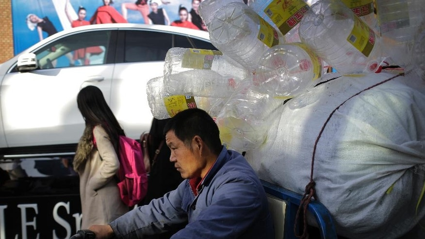 A man rides a tricycle cart loaded with recyclable bottles past a Mercedes-Benz SUV car model on display at the 798 Art Gallery for the China Fashion Week in Beijing, Monday, Oct. 26, 2015. Facing pressure to shore up sagging economic growth, Chinese leaders are gathered this week to draw up a new blueprint to guide development through the end of this decade. (AP Photo/Andy Wong)