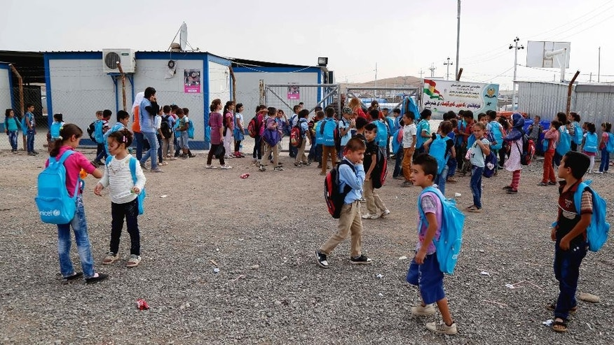 FILE - In this Wednesday, Oct. 7, 2015, file photo, students prepare to go to the school at the Kawergosk refugee camp, in Irbil, northern Iraq. With the school year just kicking off in Iraq, schools like this one are scrambling to accommodate the refugee students left behind. Nine of Kawergosk's teachers fled to Europe this summer and the remaining teachers are doubling up on students. (AP Photo/Seivan M. Salim, File)