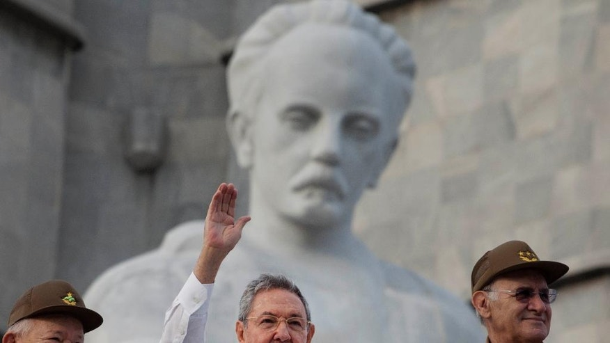 "FILE - In this May 1, 2013 file photo, Cuba's President Raul Castro, center, waves to people attending a May Day march as he stands with Commander Guillermo Garcia Frias, left, and Interior Minister Abelardo Colome Ibarra as they stand in front of the Jose Marti monument at the Revolution Square in Havana, Cuba. Colome Ibarra, a historic revolutionary fighter who accompanied the Castro brothers when they toppled dictator Fulgencio Batista in 1959, has resigned for health reasons. A communique read Monday, Oct. 26, 2015 on state television said that President Raul Castro had accepted the resignation of the veteran revolutionary, soldier and intelligence official known by his nickname ""Furry."" (AP Photo/Ramon Espinosa, File)"