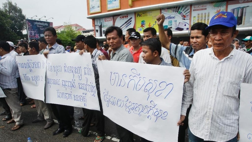 "Pro-ruling party demonstrators stage a protest rally in front of National Assembly in Phnom Penh, Cambodia, Monday, Oct. 26, 2015. Two members of Cambodia's opposition party have been beaten up outside the National Assembly allegedly by protesters who were demanding that the deputy opposition leader step down from his post of parliament's vice president. Banners, center, read: ""Kem Sokha is persuaded the Khmer isolated,"" right, ""Kem Sokha is making Khmer with no happiness."" (AP Photo/Heng Sinith)"