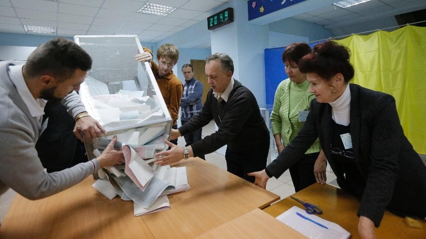 Members of a local election commission open a ballot box to count votes after a day of election at a polling station in Kiev, Ukraine, Sunday, Oct. 25, 2015. (AP Photo/Sergei Chuzavkov)