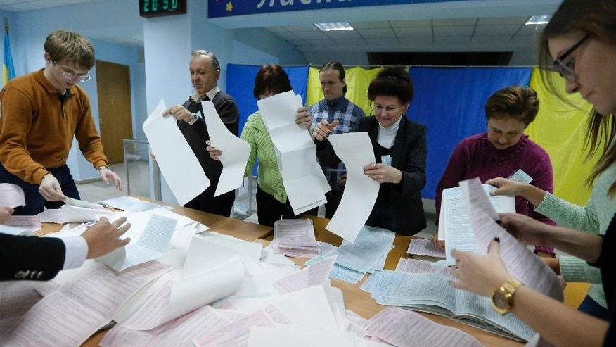 Members of a local election commission count ballots at a polling station in Kiev, Ukraine, Sunday, Oct. 25, 2015. (AP Photo/Sergei Chuzavkov)