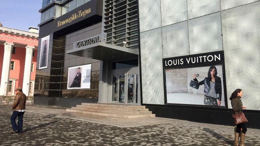 Residents walk past high end boutique shops in Ulaanbaatar, Mongolia, Monday, Oct. 26, 2015. In the capital, a growing urban population is buying upscale cashmere and foreign clothing brands. On the edge of Chinggis Square - named after national founding father Genghis Khan - luxury brands Louis Vuitton and Ermenegildo Zegna already have set up boutiques. (AP Photo/Grace Brown)