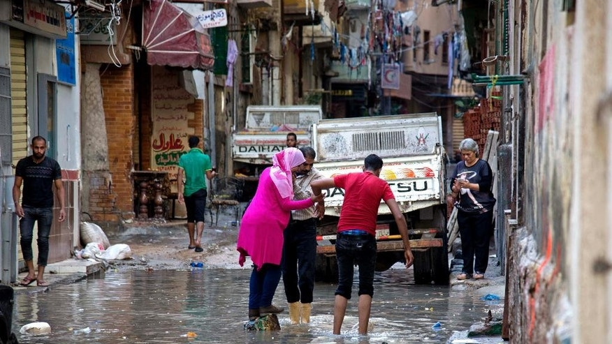 Egyptians walk through water after a heavy rainfall in the coastal city of Alexandria, Egypt, Sunday, Oct. 25, 2015. Severe weather swept across the Middle East on Sunday, pounding Israel with baseball-sized hail, sending torrents of uncollected garbage through the streets of Beirut and killing six people in Egypt, five of whom were electrocuted by a fallen power cable. The cable from a tramway landed in streets flooded with water, electrocuting the five, senior health official Magdy Hegazy said. (AP Photo/Heba Khamis)
