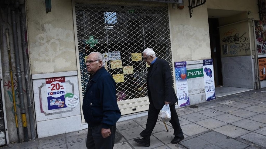 People walk past a shuttered pharmacy during the first day of a strike by the pharmacy owners association in the northern Greek city of Thessaloniki, Monday, Oct. 26, 2015. Pharmacists are on strike to protest against new reforms in their sector. A leading European Union official said Monday that Greece's bailout talks with its international creditors are broadly on track, but the country still has much work to do, in little time. (AP Photo/Giannis Papanikos)