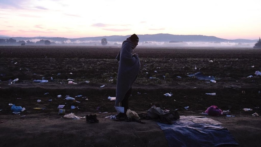 An Afghan migrant covers himself with a blanket to keep warm as he waits to pass from the northern Greek village of Idomeni to southern Macedonia Monday, Oct. 26, 2015. European leaders decide that reception capacities should be boosted in Greece and along the Balkans migration route to accommodate 100,000 more people as winter looms. (AP Photo/Giannis Papanikos)