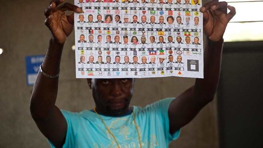 An electoral worker holds up a presidential ballot showing a vote cast for Moise Jean-Charles, of the Petit Dessalines faction, during general elections in Port-au-Prince, Haiti, Sunday, Oct. 25, 2015. Haitians faced lengthy ballots featuring 54 presidential hopefuls and a slew of legislative and municipal candidates Sunday as they selected leaders they hope can lift the nation out of chronic poverty and turbulence. (AP Photo/Dieu Nalio Chery)