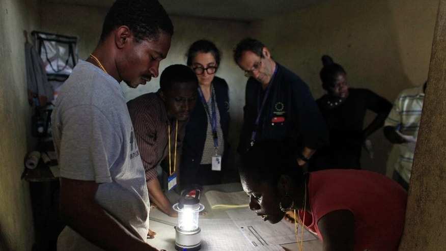 Members of the European Union Election Observation Mission observe electoral workers count ballots at a polling station at the end of the general elections, in Port-au-Prince, Haiti, Sunday, Oct. 25, 2015. The country held the first-round presidential vote Sunday along with balloting for numerous legislative races and local offices. (AP Photo/Ricardo Arduengo)