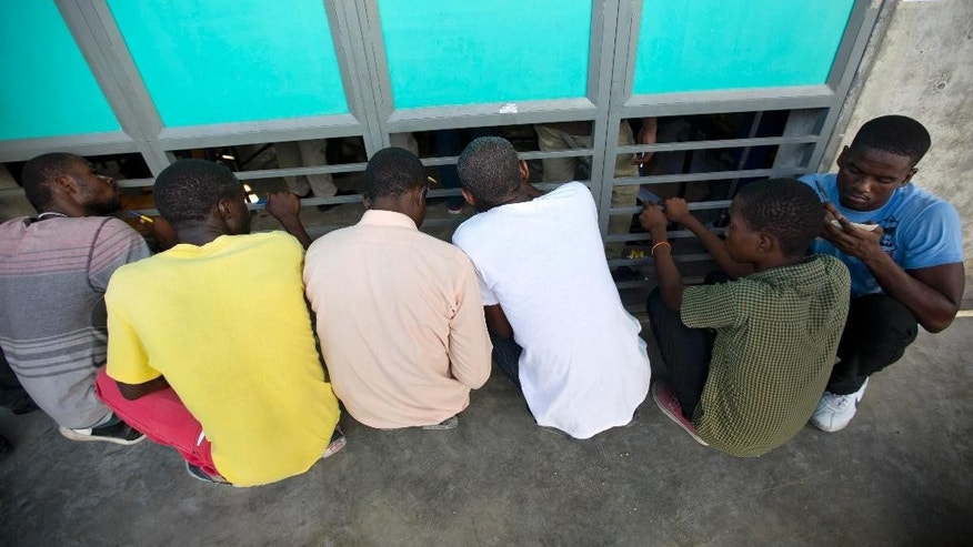 People peek through windows at a polling station to watch electoral workers count ballots during their country's general elections, in Port-au-Prince, Haiti, Sunday, Oct. 25, 2015. Haitians faced lengthy ballots featuring 54 presidential hopefuls and a slew of legislative and municipal candidates Sunday as they selected leaders they hope can lift the nation out of chronic poverty and turbulence. (AP Photo/Dieu Nalio Chery)