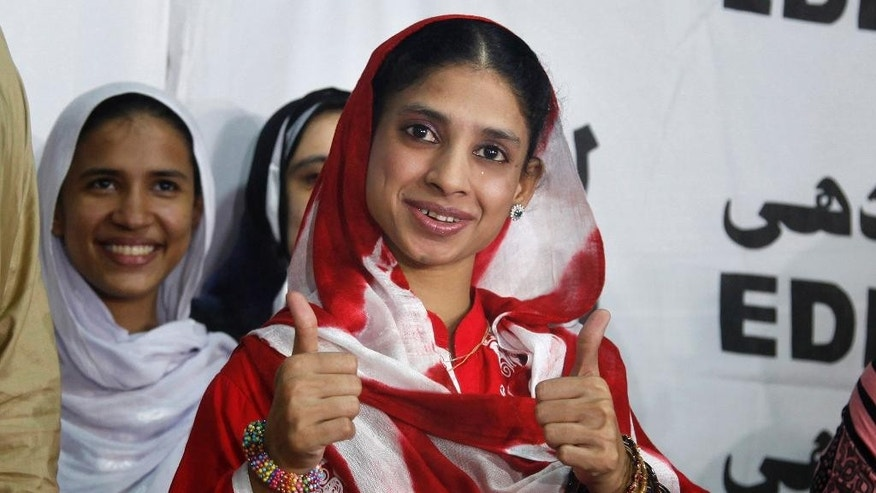 "Indian national Geeta greets media with a traditional Indian ""namaste"" prior her departure from the international airport in Karachi, Pakistan, Monday, Oct. 26, 2015. Geeta, who is deaf and mute, accidentally crossed the border into Pakistan from India as a child nearly 12 years ago, left for Delhi after Indian authorities issued her travel document, local media reported. (AP Photo/Shakil Adil)"