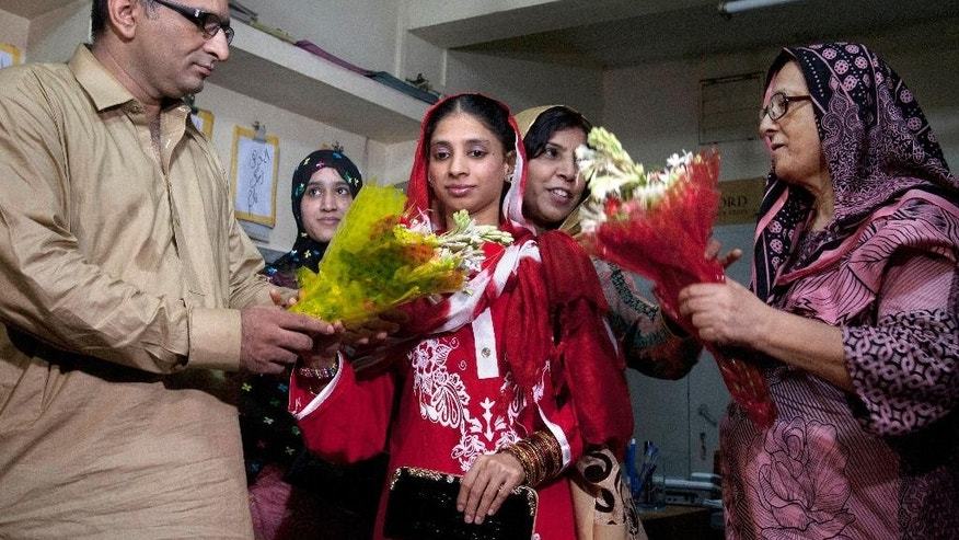 Faisal Edhi, left, head of Edhi Foundation, presents a bouquet of flowers to Indian national Geeta prior her departure from Karachi, Pakistan, Monday, Oct. 26, 2015. Geeta, who is deaf and mute, accidentally crossed the border into Pakistan from India as a child nearly 12 years ago, left for Delhi after Indian authorities issued her travel document, local media reported. (AP Photo/Shakil Adil)