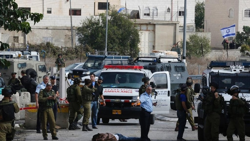 "Israeli soldiers and police stand next to the body of a Palestinian by the West Bank settlement of Kiryat Arba, Monday, Oct. 26, 2015. The Israeli military said the Palestinian stabbed an Israeli in the West Bank before being shot and killed. According to the military, the Israeli was stabbed in the neck Monday and ""severely wounded"" near the city of Hebron. (AP Photo/Wisam Hashlamoun)"