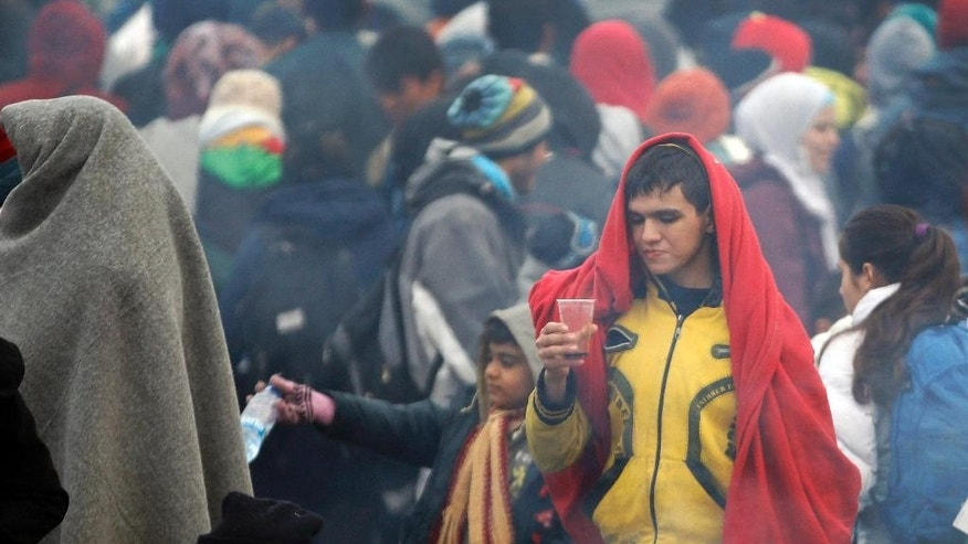 A young man hholds a cup in a crowd of hundreds of migrants waiting to enter a camp in Spielfeld, Austria, Monday, Oct. 26, 2015. Thousands of people trying to reach central and northern Europe via the Balkans often have to wait for days in the cold rain and mud at the borders. (AP Photo/Petr David Josek)