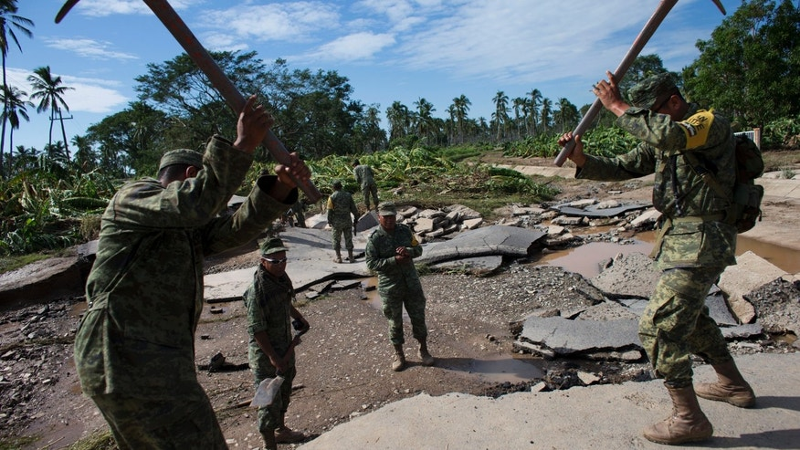 Soldiers break up a road washed away by floodwaters, to create a makeshift passage toward the village of Rebalse, near Cihuatlan, Jalisco State, Mexico, Sunday, Oct. 25, 2015. Patricia roared ashore in Mexico on Friday as a Category 5 terror that barreled toward land with winds up to 200 mph (320 kph). But the arrival of the most powerful hurricane on record in the Western Hemisphere caused remarkably little destruction. (AP Photo/Rebecca Blackwell)