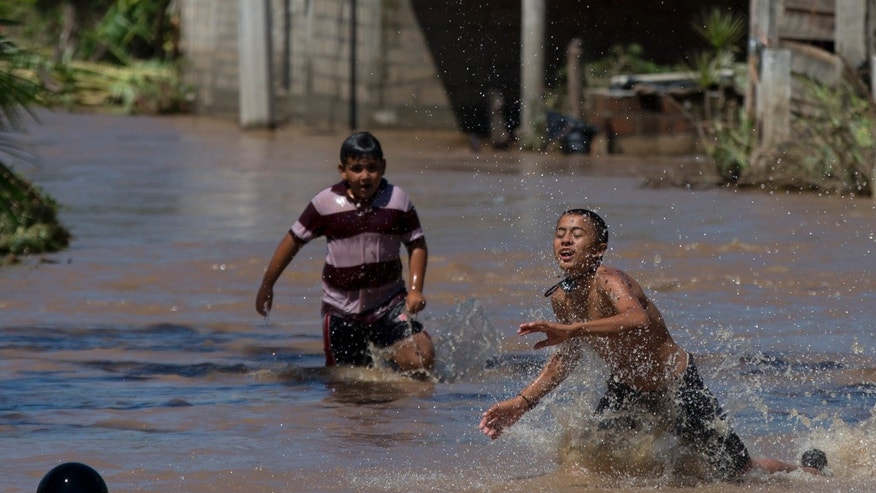 Boys play in the receding floodwaters two days after the passage of Hurricane Patricia in the village of Rebalse, Jalisco state, Mexico, Sunday, Oct. 25, 2015. Patricia roared ashore in Mexico on Friday as a Category 5 terror that barreled toward land with winds up to 200 mph (320 kph). But the arrival of the most powerful hurricane on record in the Western Hemisphere caused remarkably little destruction. (AP Photo/Rebecca Blackwell)