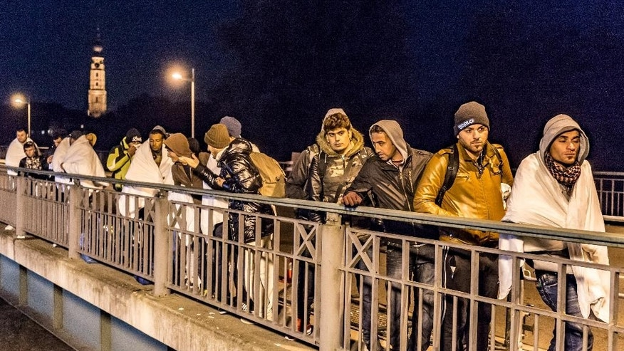 In this Oct. 25, 2015 picture migrants cross a bridge over river Inn, near the Austrian-German border near Simbach am Inn, Germany. Thousands of people are trying to reach central and northern Europe via the Balkans, but often have to wait for days in mud and rain at the Serbian, Croatian and Slovenian borders.  ( Armin Weigel/dpa via AP)